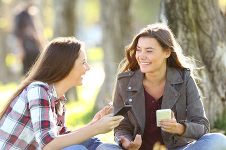Two happy friends talking and laughing holding their smart phones sitting on the grass in a park Banco de Imagens