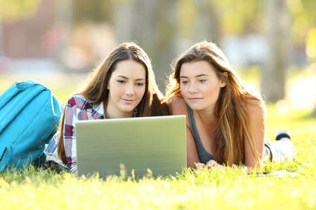 Front view of two students learning on line with laptop lying on the grass in an university campus