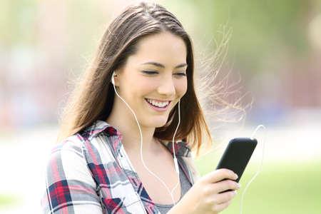 music lyrics: Adolescente niña escuchar música con auriculares y caminar en la calle Foto de archivo