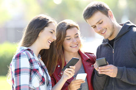 Three happy teen friends sharing smart phone content outdoors Фото со стока