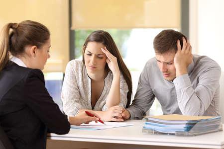 Verkoopster die voorwaarden van een document met slecht nieuws verklaart aan een paar bezorgde klanten op kantoor