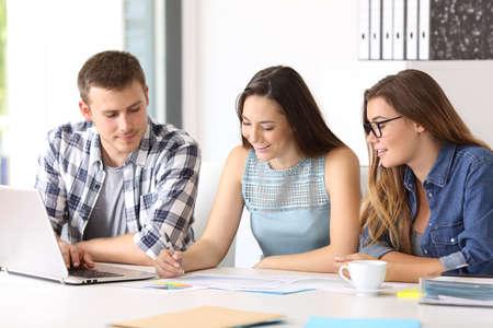 Tre impiegati felici collaborano a leggere i documenti in ufficio