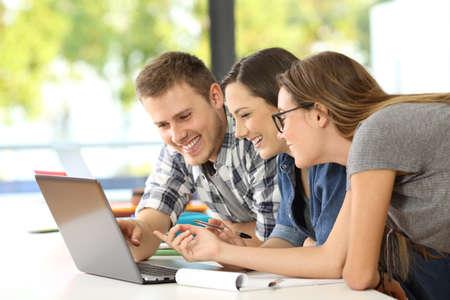 Tres estudiantes felices jugando juntos en línea con una computadora portátil en un aula Foto de archivo - 82408244