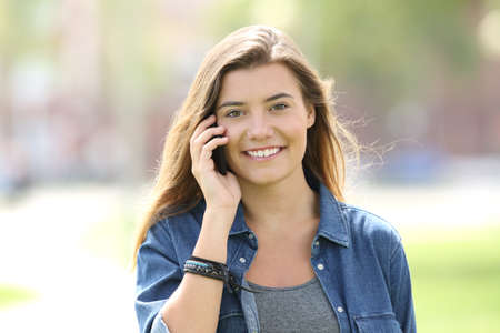 Front view of a single teen girl walking towards camera and calling on phone looking at you in the street Stock Photo