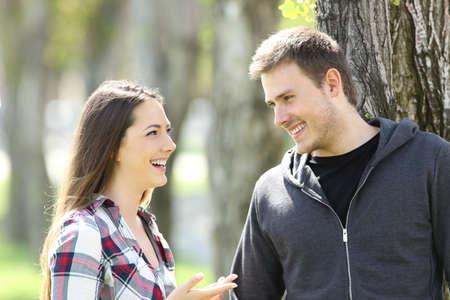 Twee gelukkige tienervriendjes praten en elkaar in een park kijken Stockfoto