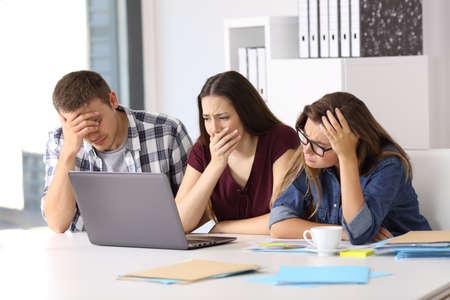 Drie bezorgde zakenlieden die line-content kijken in een laptop op kantoor