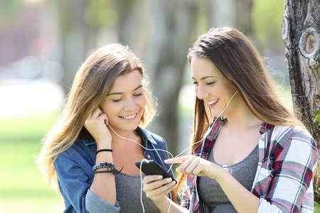 Two happy teen friends listening music sharing earphones and smartphone in a park