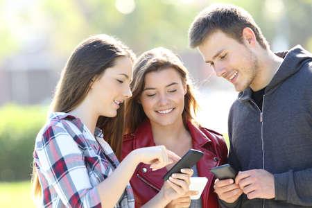 Tres amigos de pie y compartir contenido en línea con sus teléfonos inteligentes en la calle Foto de archivo - 82408272