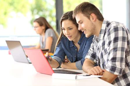 Dos estudiantes concentrados que estudian en línea juntos que se sientan en una mesa en un aula con un compañero de clase en el fondo Foto de archivo