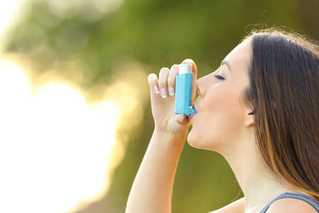 Side view of a woman using an asthma inhaler outdoors with a green background Imagens