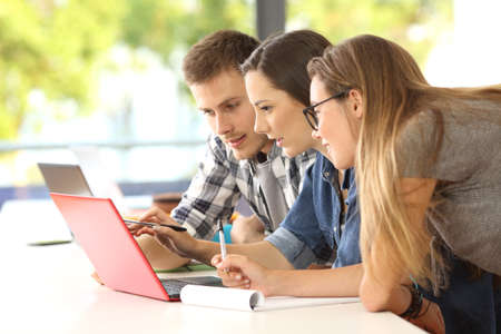 Three concentrated students studying together on line with a laptop in a desk at classroom