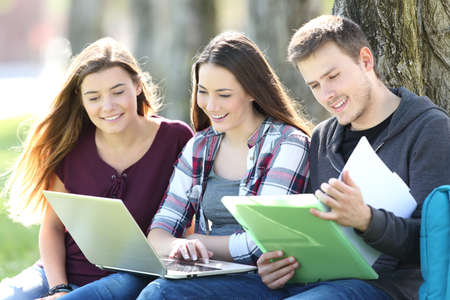 Three happy students studying on line with a laptop and reading notes sitting on the grass in a park Stockfoto