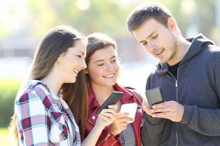 Three friends talking together and holding everyone their smart phones standing in the street