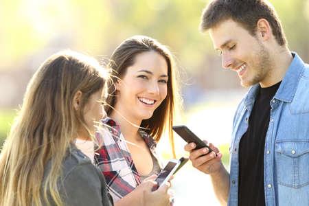 자신의 스마트 폰을 사용하는 3 대 청소년과 그 중 한 명은 거리에서 나를 보았습니다. 스톡 콘텐츠