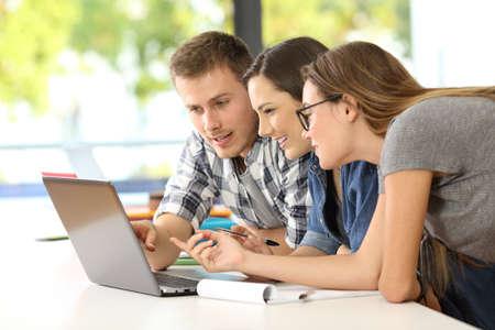 Drie studenten leren samen in lijn met een laptop in een klaslokaal Stockfoto