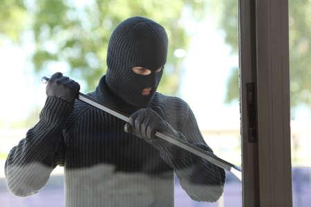 도둑이 검은 색 마스크를 쓰고 레버가있는 집 창을 열려고 시도하다.