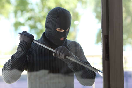 Thief wearing black mask trying to open a house window with a lever Stockfoto