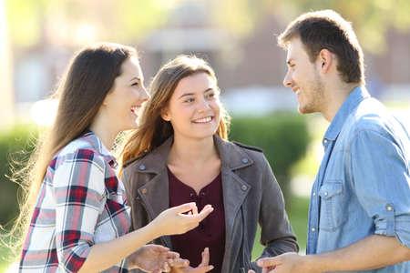 Tres amigos felices teniendo una conversación y riendo en la calle Foto de archivo - 82408322