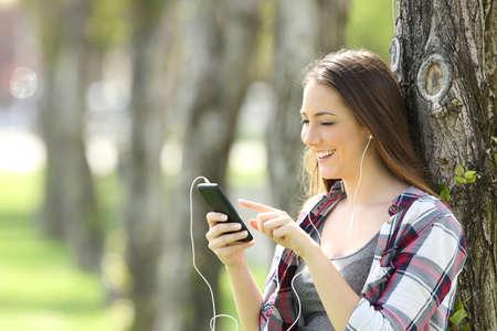 music lyrics: Muchacha adolescente hermosa que escucha y que elige la música en un teléfono elegante que se inclina en un árbol en un parque