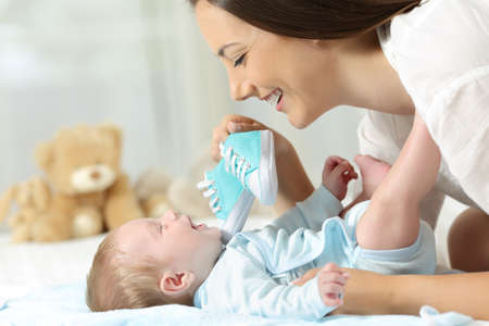 babysit: Happy mother showing a new shoes to her baby on a bed at home
