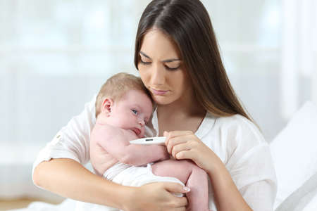 Mother using a thermometer th check temperature of her ill baby at home
