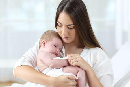 Matka za pomocą termometru th sprawdzić temperaturę chorego dziecka w domu