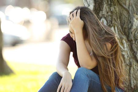 Single sad woman lamenting sitting in a park