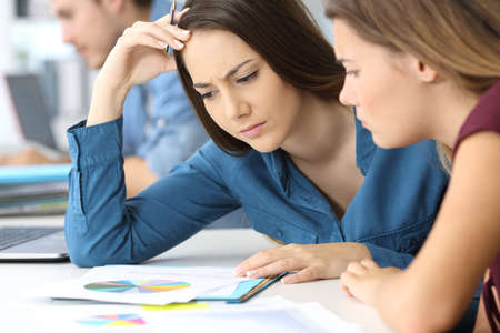 Two confused businesswomen checking paper documents at office Stock Photo