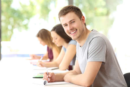 Happy student boy posing in a classroom looking at you
