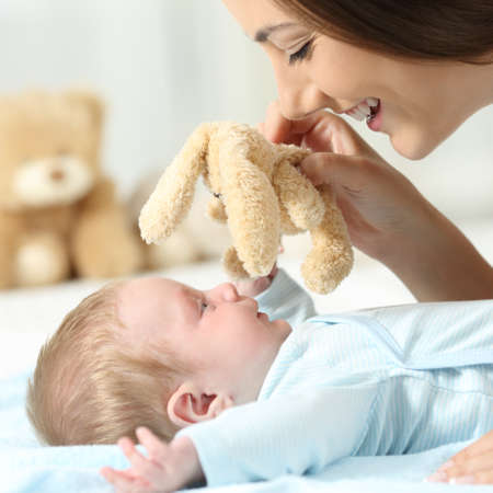 babysit: Side view close up portrait of a mother playing with her baby holding a teddy on a bed Stock Photo