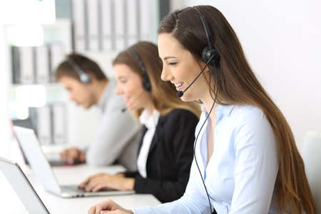 Side view of a telemarketer working on line at office with other workers in the background