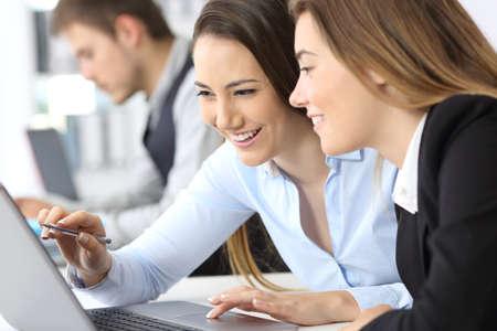Dos empresarias trabajando juntos en línea con un ordenador portátil en la oficina Foto de archivo - 83131668