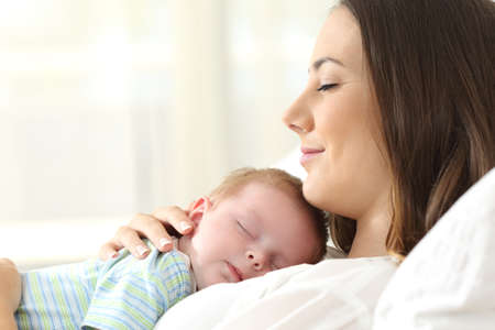 Profile of a happy mother sleeping with her baby on a bed at home Stok Fotoğraf