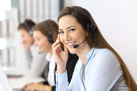 Happy telemarketer looking at you at office with other workers in the background