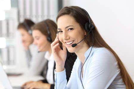 Happy Telemarketer Blick auf Sie im Büro mit anderen Arbeitnehmern im Hintergrund Standard-Bild