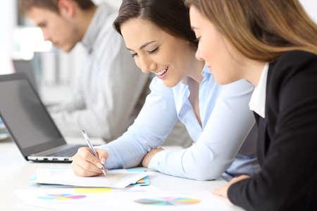 Close-up van twee gelukkige zakenvrouwen die samenwerken op kantoor
