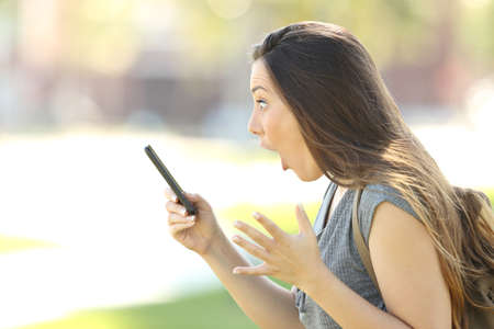 Side view of a single amazed woman using a mobile phone outdoors in the street