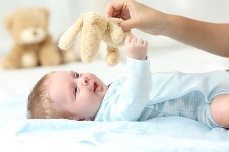 babysit: Mother hand holding a teddy and playing with her baby son on a bed