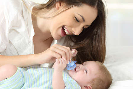 Happy mother giving a pacifier to her baby on a bed