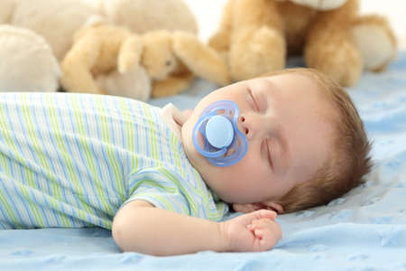 Cute baby sleeping with a pacifier on a bed