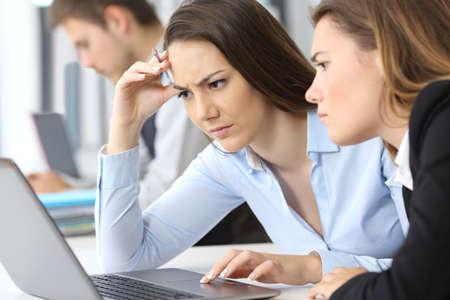 Dos empresarias preocupadas trabajando en línea con un ordenador portátil en la oficina Foto de archivo - 83107765