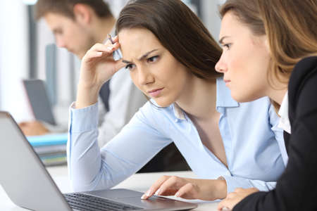 Two worried businesswomen working on line with a laptop at office Stok Fotoğraf