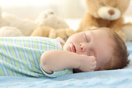 babysit: Portrait of a cute baby sleeping on a bed Stock Photo