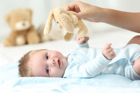 babysit: Mother hand holding a teddy and her baby looking at you on a bed