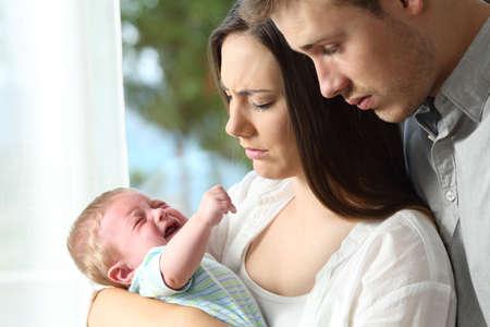 疲れて必死の親家で必死に泣いている赤ちゃんを保持 写真素材