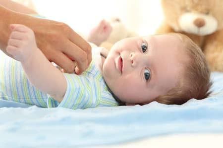 Porträt eines glücklichen Baby Blick auf Sie und eine Mutter Hand berühren ihn Standard-Bild - 83953288