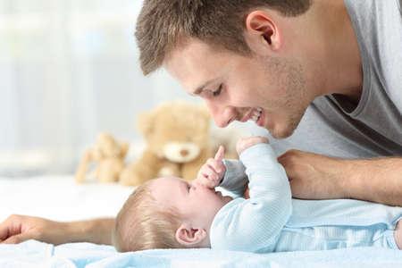 Zijaanzicht portret van een baby en vader samen spelen op een bed Stockfoto