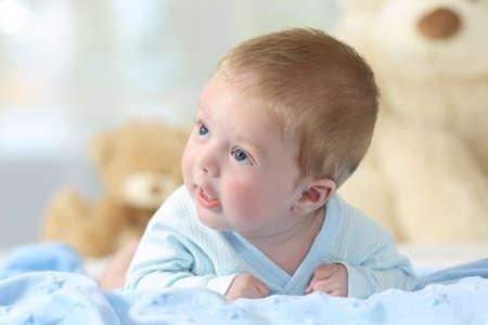 Porträt eines Babys, das Seite auf einer blauen Decke in einem Bett betrachtet Standard-Bild - 83953309