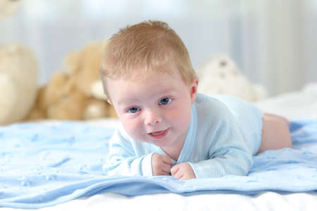 Portrait eines Babys versucht, in Richtung Kamera auf eine blaue Decke zu kriechen Standard-Bild - 83953311