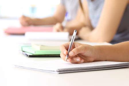 Primer plano de una mano de estudiante tomando notas en un bloc de notas en el aula Foto de archivo - 83953315